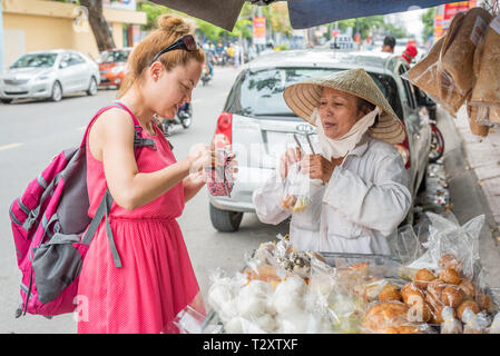 Nha Trang, Vietnam - May 5, 2018: A solo woman traveler buys sweets from a Vietnamese lady in an Asian conical hat who sells desserts out of her cart. - Stock Photo