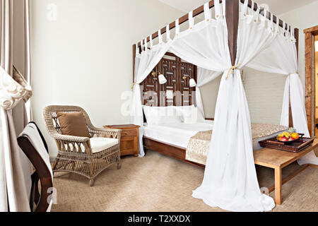 Hotel room - vacation concept background - Luxurious modern bedroom interior with canopy bed - Stock Photo
