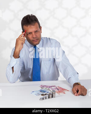 A latin man sitting in front of a group of bills and coins with an thinking or calculating expression on his face - Stock Photo
