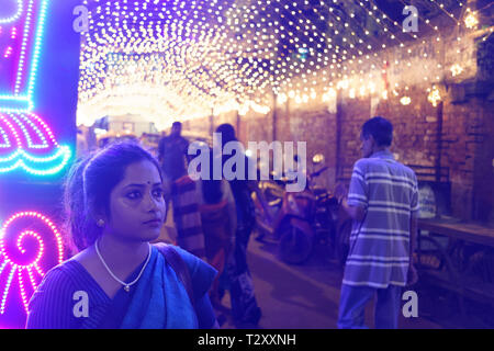 Indian Bengali lady on street full of lights in a festive evening - Stock Photo
