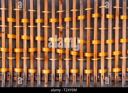 An unknown artist weaves golden ribbon through fence slats; Salida SteamPlant Event Center; Salida; Colorado; USA