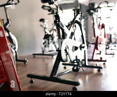 Aerobics spinning exercise bikes at gym room - Stock Photo