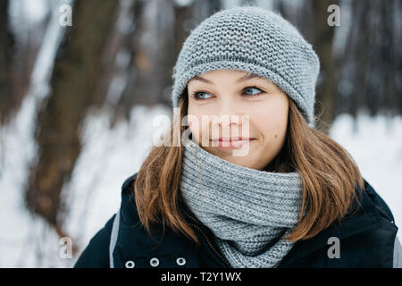 Portrait of smiling young woman wearing scarf and hat in winter park Stock Photo