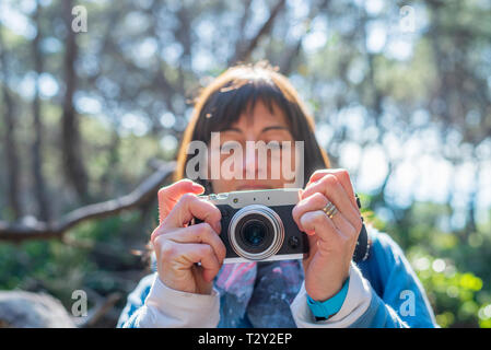 Portrait of young woman taking photos in autumn - Stock Photo