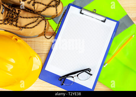 High visibility vest with work boots and yellow hard hat along side a blue clipboard with black rimmed spectacles - Stock Photo
