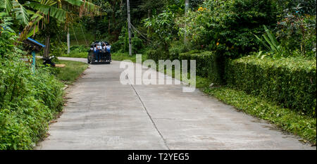 Students riding to school in small Thai village on pickup truck - Stock Photo