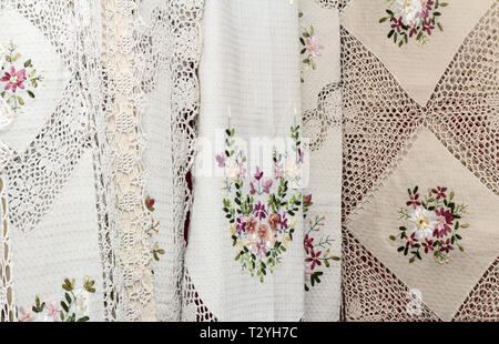 In the shop window of the beautiful tablecloths and napkins of flax, decorated with beautiful lace and embroidery. - Stock Photo