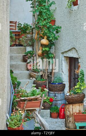 Old lane with flower decoration, ancient fort city, Lubenice, Island Cres, Croatia - Stock Photo