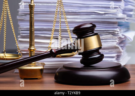 Justice Scales And Wooden Gavel In Front Of Stacked Paper On Wooden Desk - Stock Photo