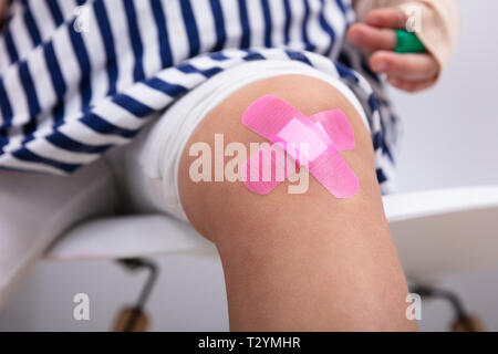 Close-up Of Girl Knee With An Pink Adhesive Bandage - Stock Photo