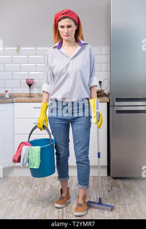 young attractive stressed service woman in washing rubber gloves carrying cleaning bucket broom and mop frustrated and overworked looking tired and la - Stock Photo