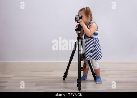 Small Innocent Girl Standing On Floor Taking Photo With Camera And Tripod - Stock Photo