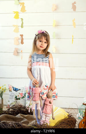 A sad little girl in a dress with flowers on her head is standing in a nest and holding cute toy rabbits by the ears. - Stock Photo