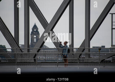 Young woman taking a photograph on Stanley Dock Bascule Bridge, Liverpool - Stock Photo