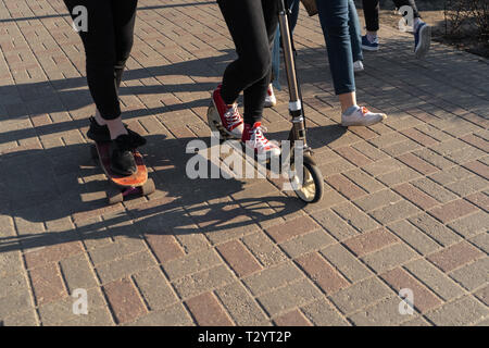 Young people in jeans and sneakers skating and using a scooter on a concrete brick pavement - Sunny weather - Stock Photo