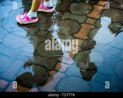 Children walk through swampy areas on floor - Stock Photo