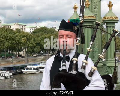 LONDON, ENGLAND, UK - SEPTEMBER 17, 2015: a bagpipes payer performs on a bridge over the river thames in london, england - Stock Photo