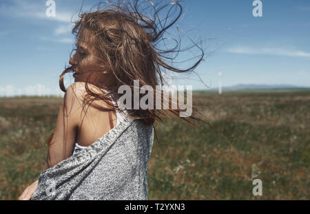 Woman with long tousled hair next to the wind turbine with the wind blowing - Stock Photo