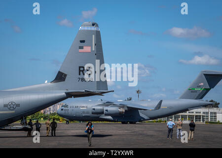 A U.S. Air Force C-17 assigned to the 16th Airlift Wing, Joint Base Charleston, Charleston, South Carolina, taxies into position as a U.S. Air Force C-130J Hercules assigned to the 75th Expeditionary Airlift Squadron, Combined Joint Task Force-Horn of Africa (CJTF-HOA) is loaded with aid from the United Nations International Children's Emergency Fund (UNICEF), at the airport in Maputo, Mozambique, April 4, 2019. The task force is helping meet requirements identified by USAID assessment teams and humanitarian organizations working in the region by providing logistics support and manpower to USA - Stock Photo