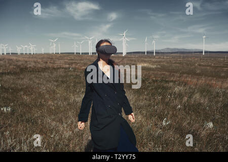 Woman wearing VR headset at the field next to the wind turbines - Stock Photo