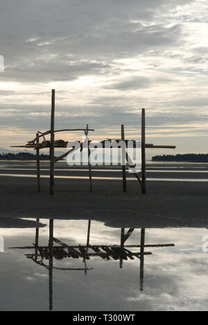 A Lonely Driftwood Structure Stands Guard over the Mud Flats at Parksville, British Columbia, Canada - Stock Photo