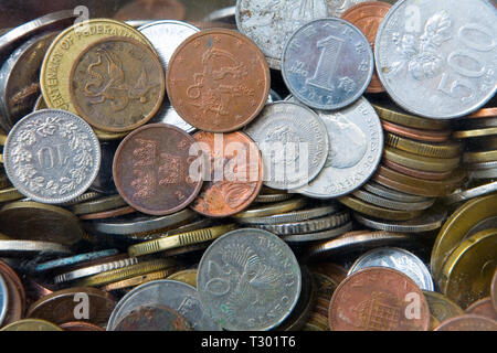 A lot of coins of various denominations and different countries. Donations in the Temple of the Big Buddha in Phuket. Thailand. - Stock Photo