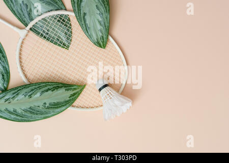 Badminton beach set and tropical leaves. Sports header on a cream background with copy space. Summer vacation flat lay - Stock Photo