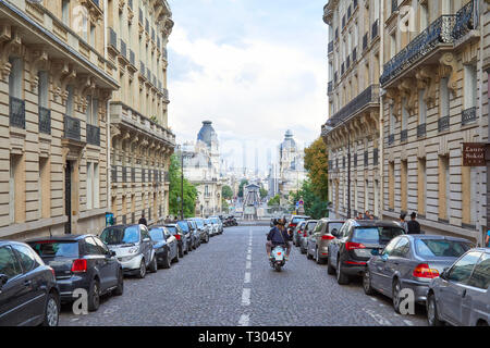 PARIS, FRANCE - JULY 22, 2017: Street in Paris with perspective, man and woman riding moped in France - Stock Photo