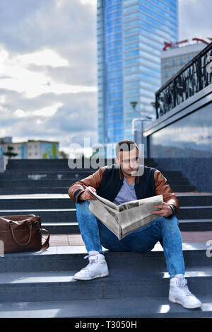 portrait of young guy in leather jacket reading newspaper in the city. man is sitting on the steps ofladder. next is bag. tall buildings in the backgr - Stock Photo
