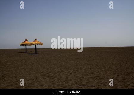 Two isolated reed umbrellas contrasting with black lava sand on lonely beach - Cobquecura Piedra De La Loberia, Chile - Stock Photo