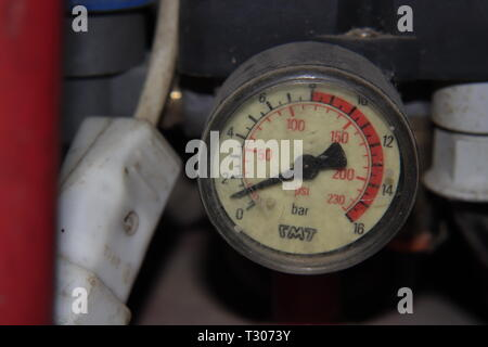 The pressure gauge on an air compressor in a messy garage. - Stock Photo