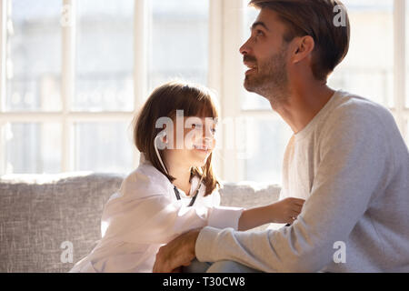 Little girl wearing white coat as doctor play with father - Stock Photo