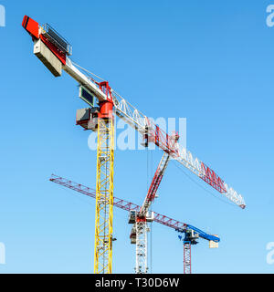 Low angle view of three large tower cranes on a construction site against blue sky. - Stock Photo