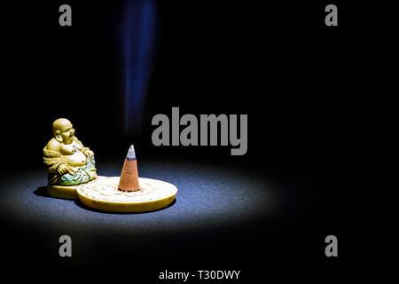 Buddha figurine with incense - Stock Photo