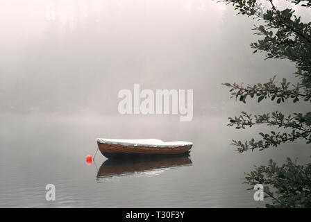 A row boat anchored on the calm lake in the foggy autumn. - Stock Photo