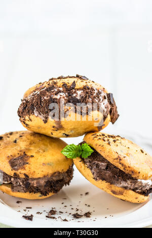 Vanilla and Chocolate Ice Cream Sandwich, Ice Cream between Two Cookies, Light Background - Stock Photo