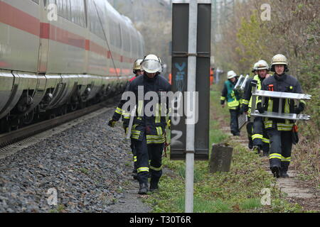 05 April 2019, North Rhine-Westphalia, Düsseldorf: An ICE of the Deutsche Bahn stands near the main station after the overhead line has been torn down. The firefighters wear bridge parts to connect the ICE with the replacement train. Photo: David Young/dpa - Stock Photo