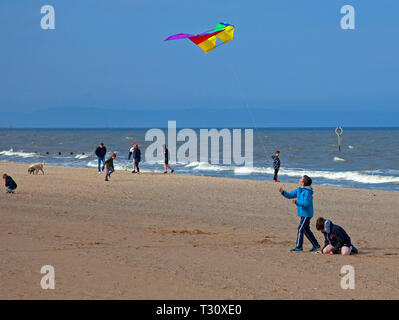 Portobello, Edinburgh, Scotland, UK. 5th Apr, 2019. UK weather, children playing with a colourful kite on a sunny cloudy and windy start to the Edinburgh Easter School holidays when school's are closed from Monday 8th to 22nd April. Temperature 13 degrees with winds of 32 km/h potential gusts of 52 km/h. - Stock Photo
