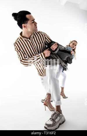 Promoting new brand. Two professional models wearing white trousers promoting new brand of clothes - Stock Photo