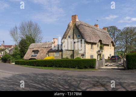 The Old Vicarage, a detached period property with thatched roofs, in the village of Potterspury, Northamptonshire, UK - Stock Photo