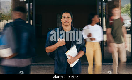 Male student at college campus with young people walking by in motion blur. Confident student standing with his backpack and book looking at camera. - Stock Photo