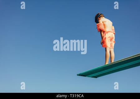 Low angle shot of boy with sleeves floats on diving board preparing for dive in the pool. Boy standing on diving spring board against sky. - Stock Photo