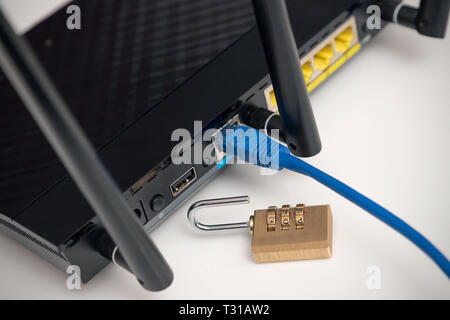Network and data protection concept with padlock. Internet router or switch with cable plugged in. - Stock Photo