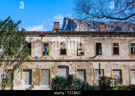 Building in Mostar damaged by the war and still not renovated. Ruined by bullet holes, mortar bomb shell grenade damage - Stock Photo