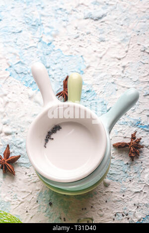 Vertical photo with top view on three small bowls or cups. Cups have simple holder. Each cup has different color - white, blue and green. Spices are s - Stock Photo