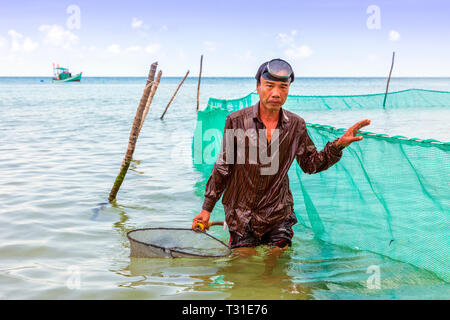 Local Vietnamese fisherman using a hand net and fishing nets off shore at Bai Dai Tay beach in the Gulf of Thailand, Phu Quoc Island, Vietnam, Asia. - Stock Photo
