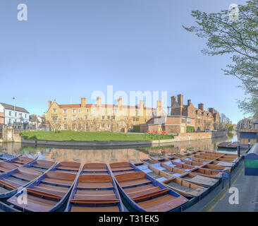 Sunshine on Magdalene college reflected in the river Cam on a sunny spring day at the university of Cambridge, England, with moored punts on the nears - Stock Photo