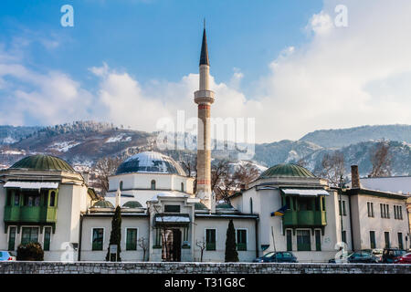 A minaret rises over buildings across the river from the Old Town neighborhood of Sarajevo. Gazi Husrev-bey Mosque.  Bosnia Herzegovina - Stock Photo