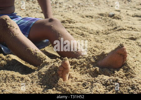 Boy in shorts with legs partly covered in sand at the beach - Stock Photo