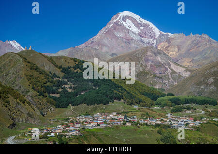 Mountain Kazbek with white snow covered peak, town of Stepantsminda in the foreground and Gergeti Trinity church on the left side with blue sky above. - Stock Photo